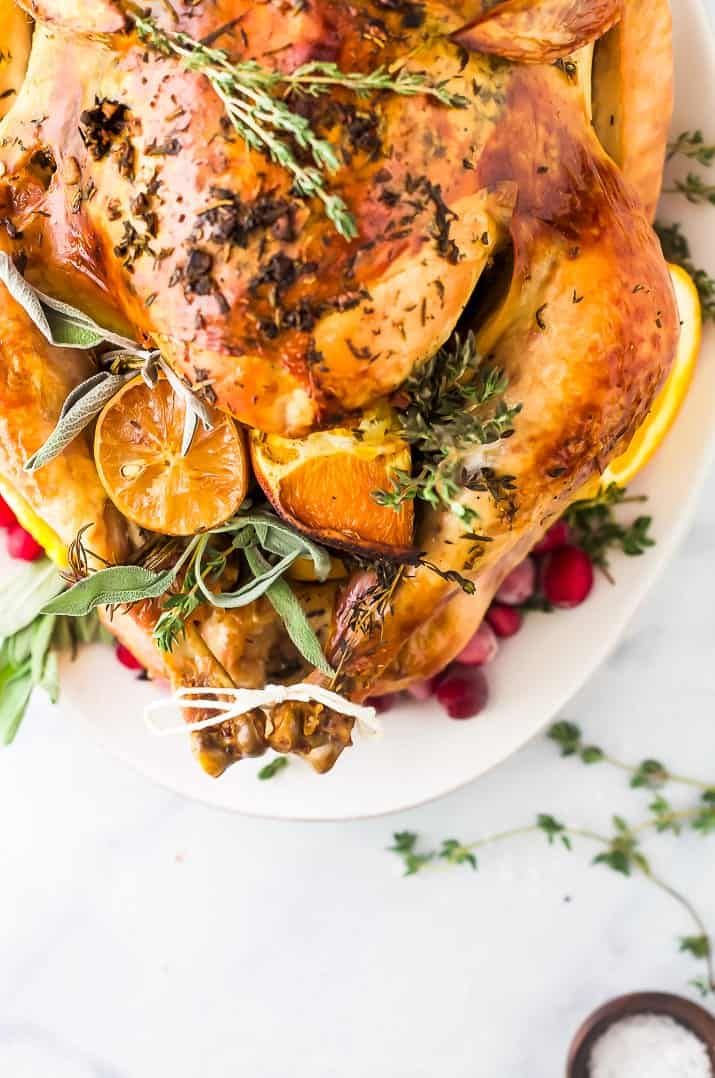 A roasted turkey cavity stuffed with orange slices and herbs