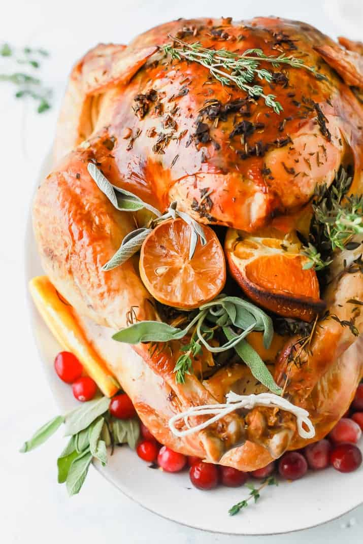 Roasted turkey on a white platter stuffed with orange slices and herbs