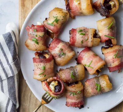 overhead photo of bacon wrapped figs with herb goat cheese on a fork and plate