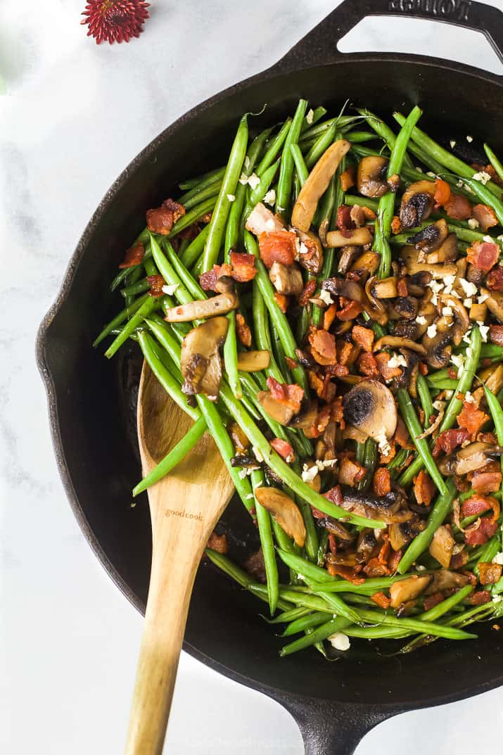 overhead photo of mushrooms and bacon on top of green beans