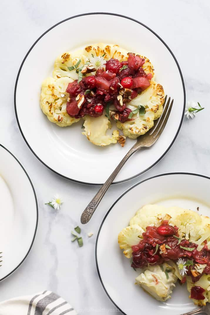 roasted cauliflower steaks with cranberry apple chutney on plates