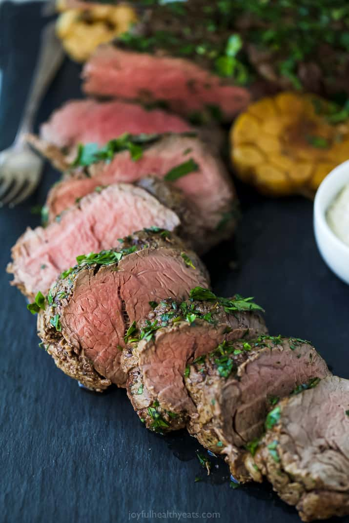 sliced herb crusted beef tenderloin roast on a serving platter