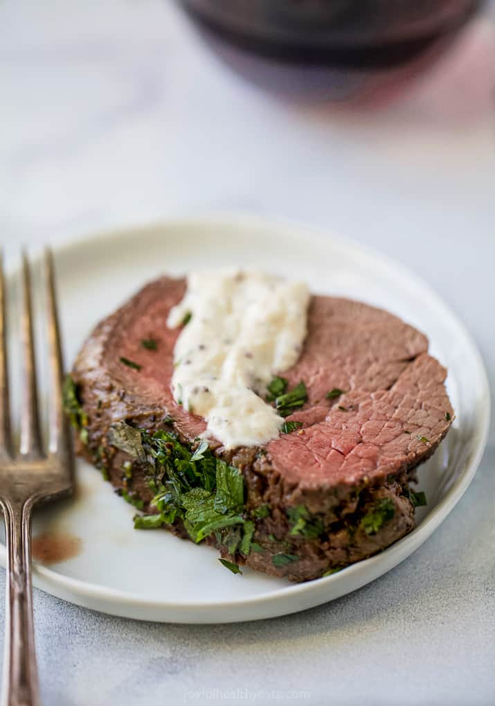 a slice herb crusted beef tenderloin roast with a dollop of horseradish sauce on a plate