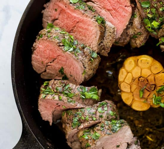 photo of beef tenderloin roast with a fresh herb crust in a cast iron skillet