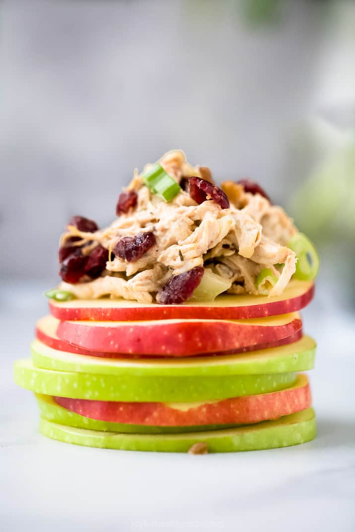 healthy cranberry chicken salad piled on top of a mound of apple slices