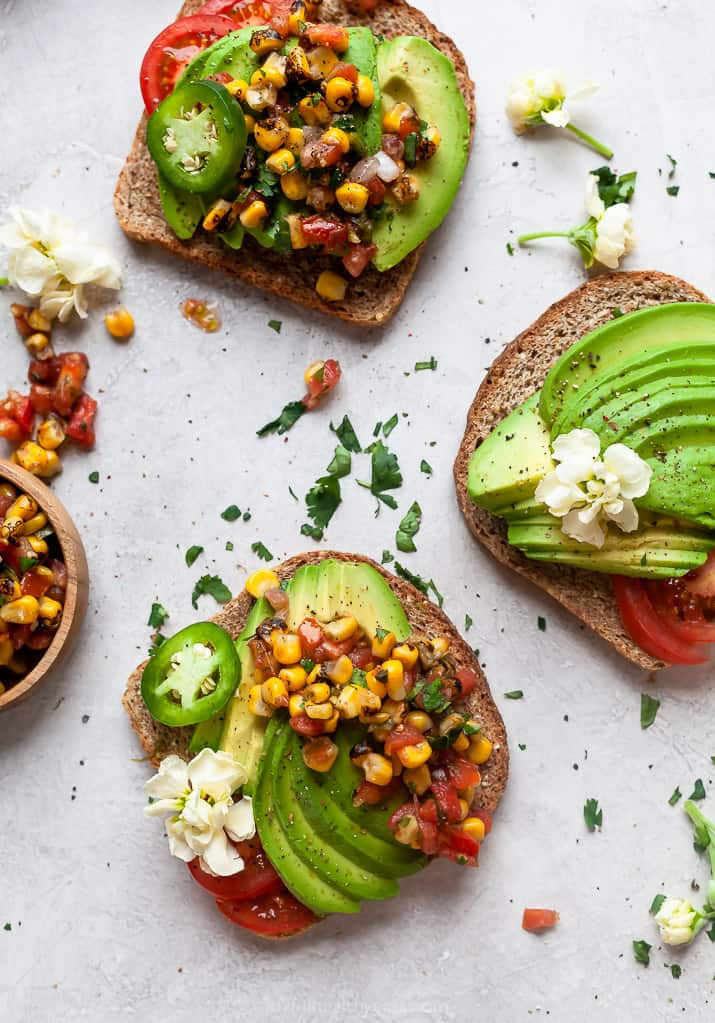 healthy avocado toast topped with charred corn salsa on a board