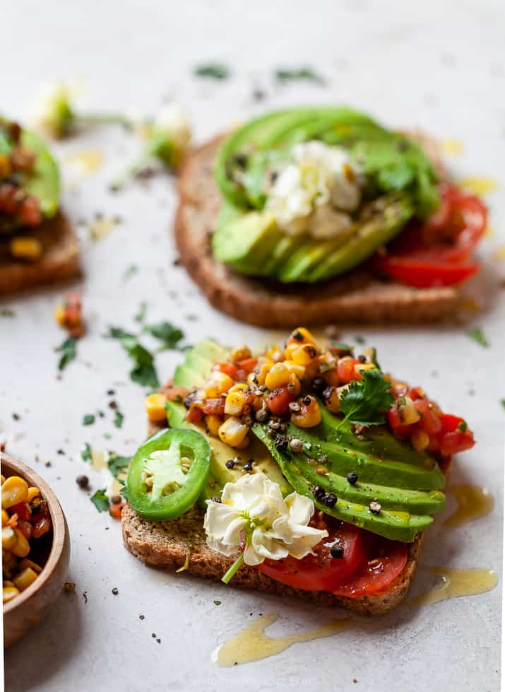 side photo of healthy avocado toast topped with charred corn salsa
