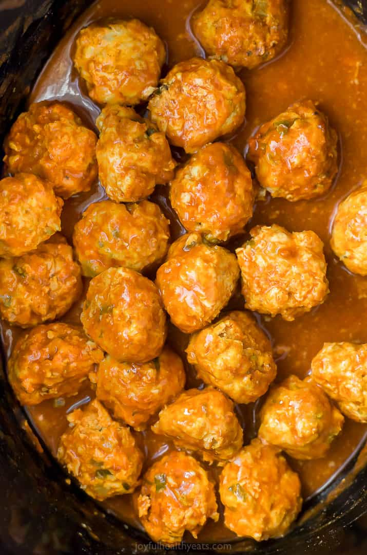 buffalo chicken meatballs covered in buffalo sauce in a crock pot