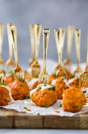 crock pot buffalo chicken meatballs drizzled with ranch dressing on a serving board