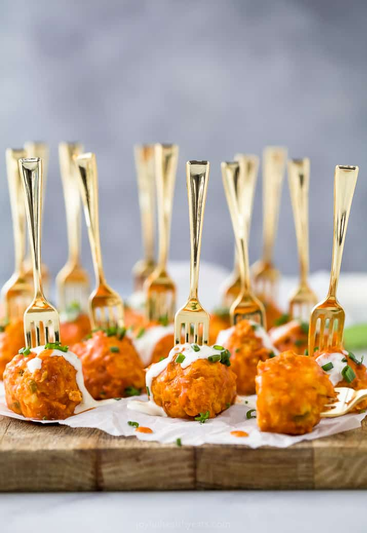crock pot buffalo chicken meatballs drizzled with ranch dressing on a small fork