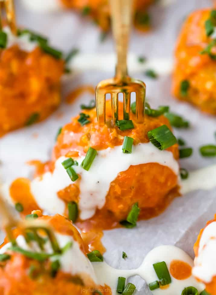 close up photo of one crock pot buffalo chicken meatball covered in ranch dressing
