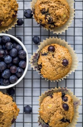 picture of healthy banana blueberry muffins on a cooling rack with a bowl of blueberries