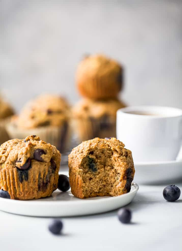 picture of healthy banana blueberry muffins on a plate, one with a bite in it