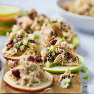 Light and Easy 15 Minute Cranberry Chicken Salad Recipe on an apple sliced served on a cutting board