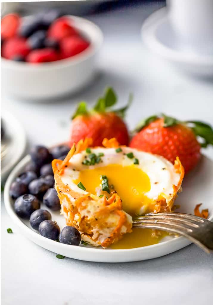a yolk being cracked in sweet potato hash baked egg cups
