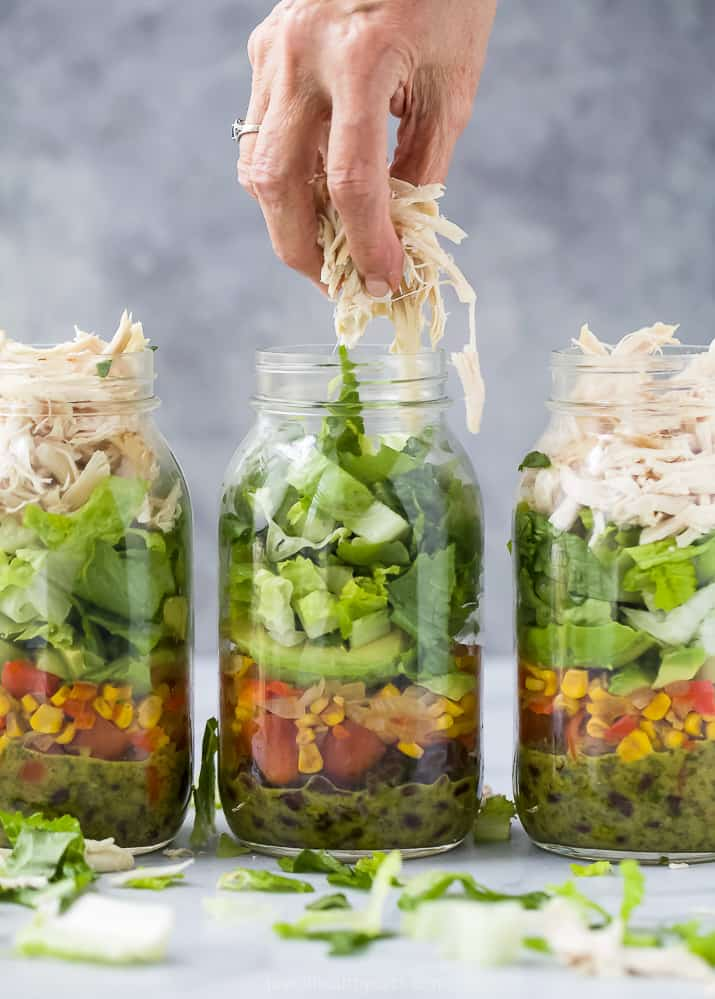 putting rotisserie chicken on top of Mason Jar Southwest Chicken Salad with Cilantro Lime Dressing