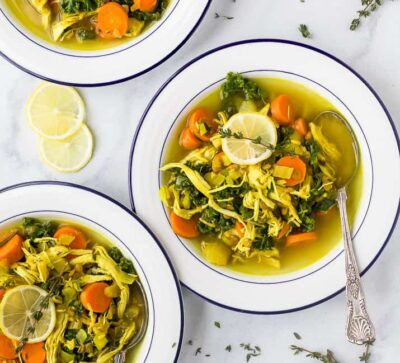 healing chicken soup recipe served in bowls topped with lemon