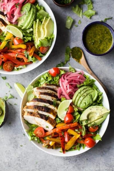 chicken fajita salad with a chimichurri dressing, pickled onions and avocado in a large bowl