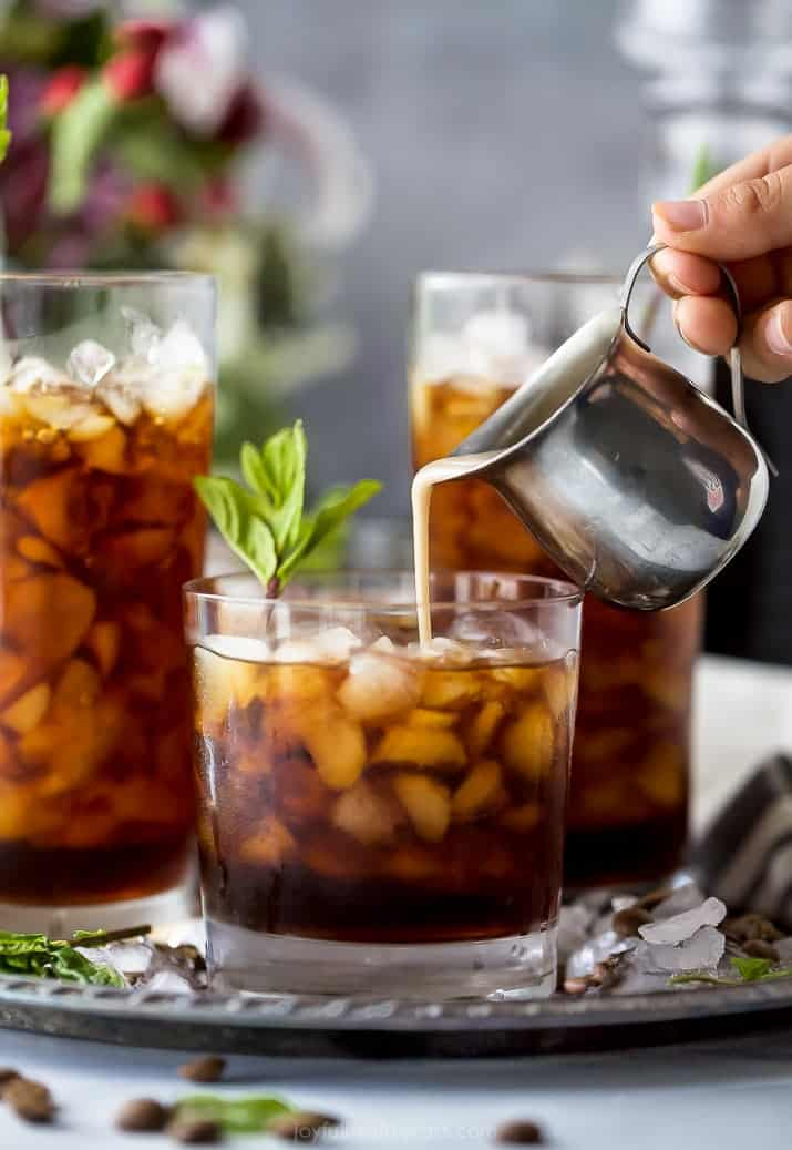 pour coconut milk creamer into thai iced coffee in a glass with mint