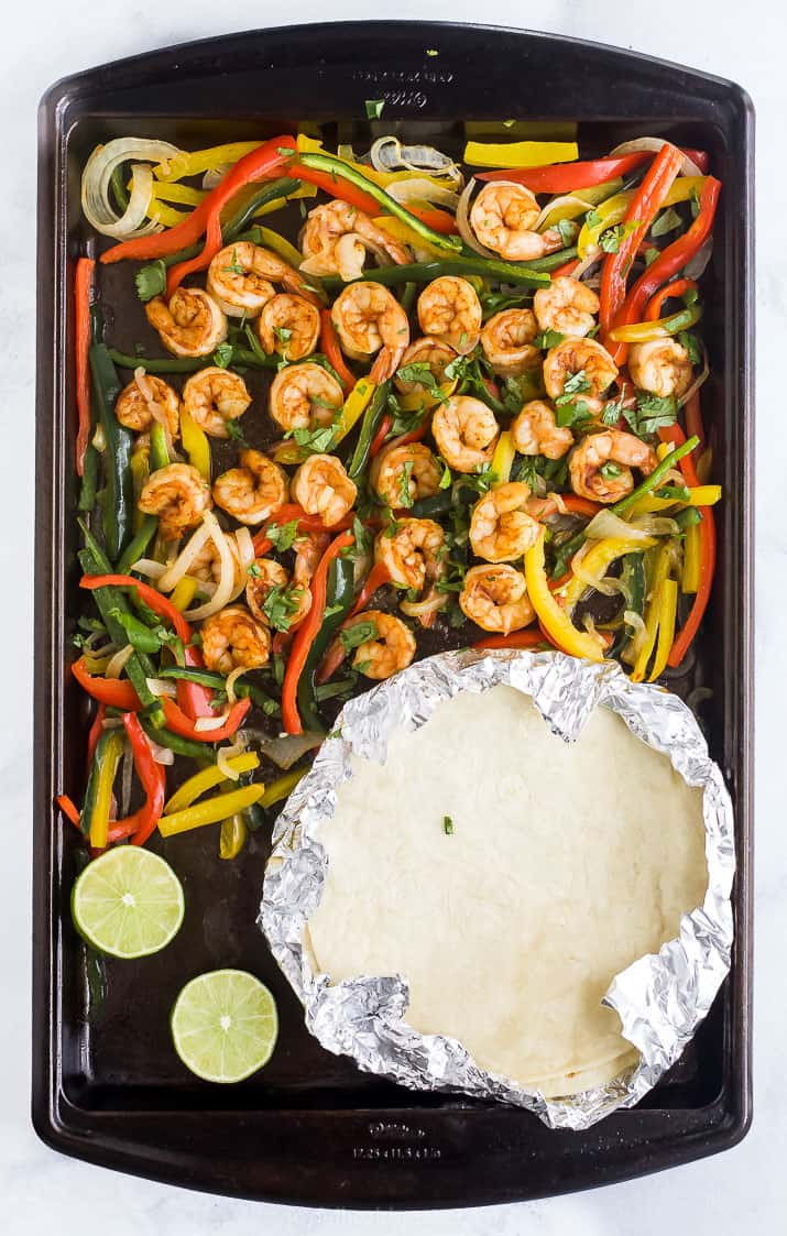 finished product of sheet pan shrimp fajitas on a baking sheet with tortillas
