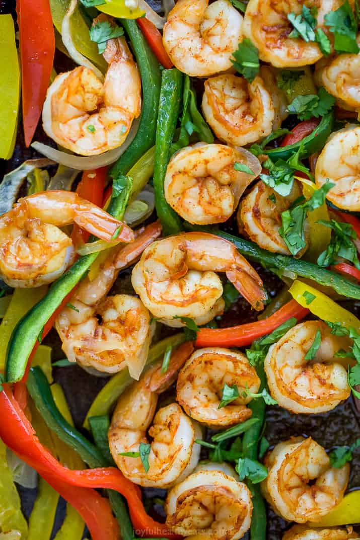 close up photo of sheet pan shrimp fajitas on a baking sheet