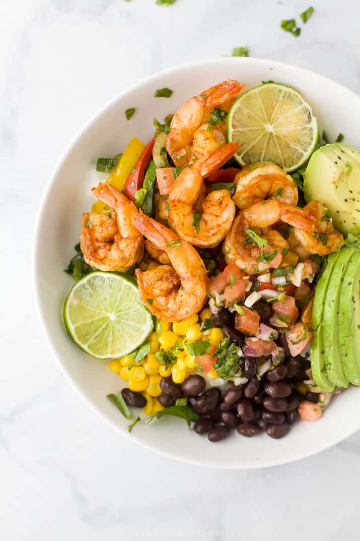sheet pan shrimp fajitas in a rice bowl with avocado, corn and pico de gallo