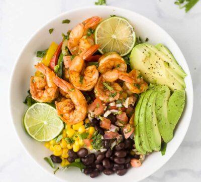sheet pan shrimp shrimp in a bowl with avocado and pice de gallo