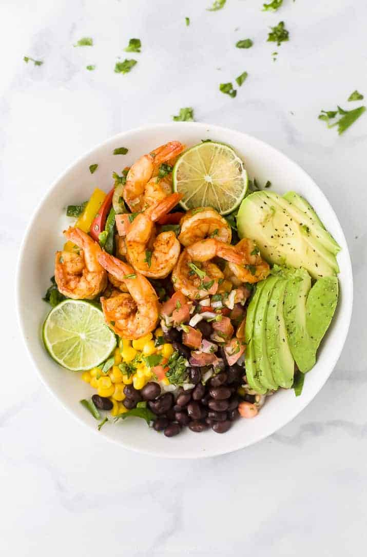 sheet pan shrimp shrimp in a bowl with avocado and pice de gallo