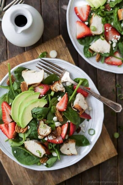 healthy strawberry avocado chicken salad with feta cheese and balsamic dressing on a plate
