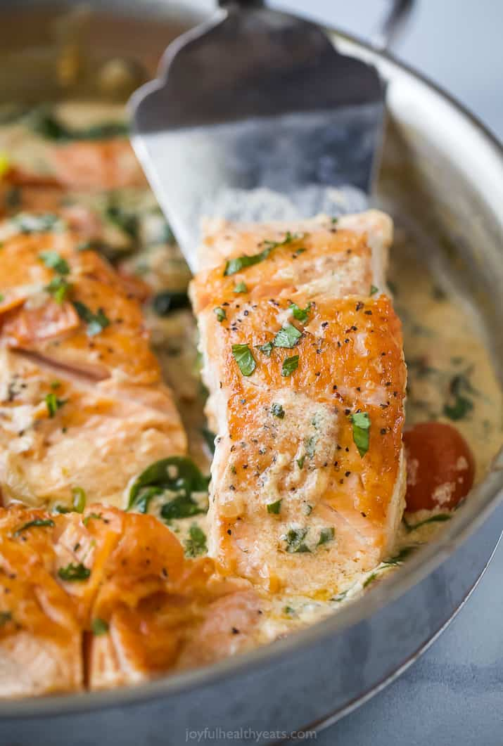 a spatula scooping creamy tuscan pan seared salmon in a skillet
