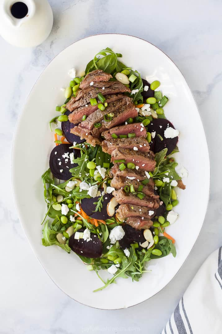 a large plate filled with roasted beet steak salad topped with goat cheese and balsamic vinaigrette