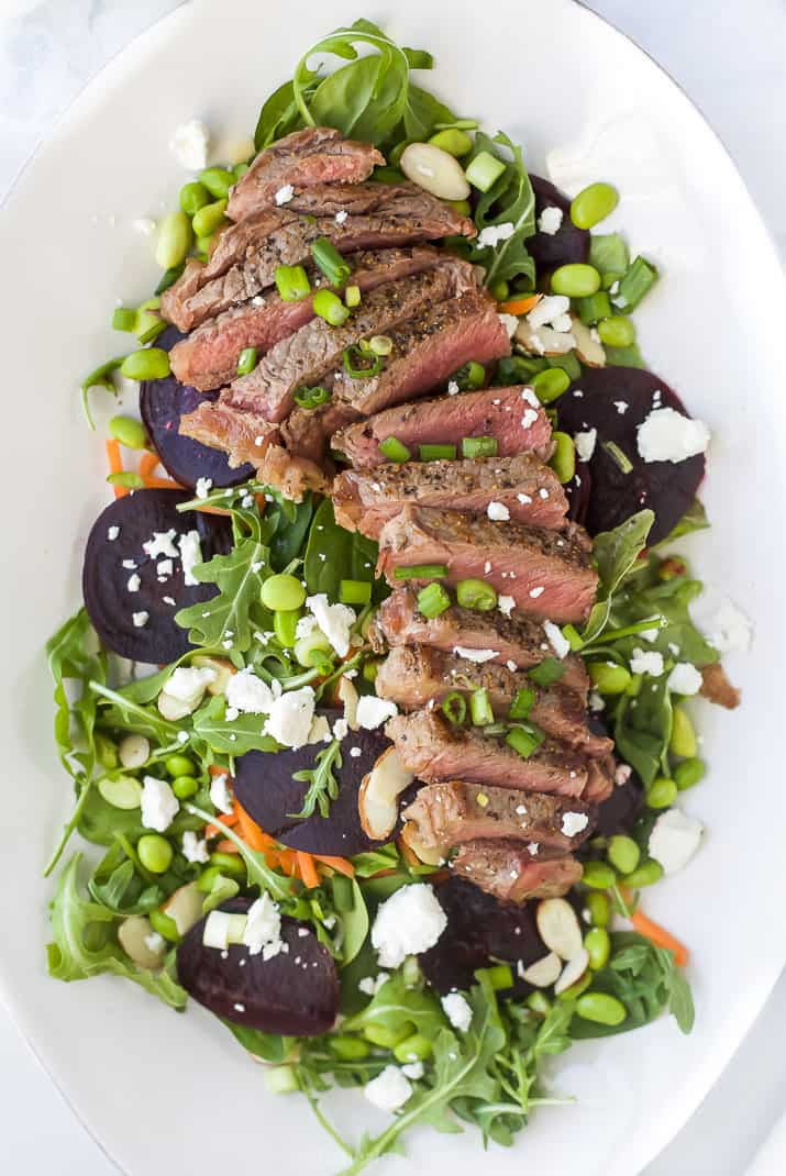 large plate filled with roasted beet steak salad topped with goat cheese