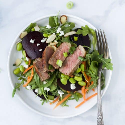 roasted beet steak salad with goat cheese and almonds on a plate