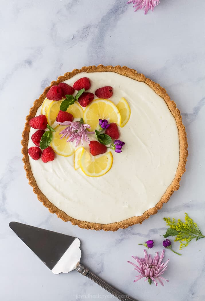 Creamy Lemon Tart Recipe with Almond Crust with flowers and berry on top