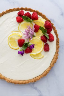 Creamy Lemon Tart Recipe with Almond Crust with flowers and fruit on top