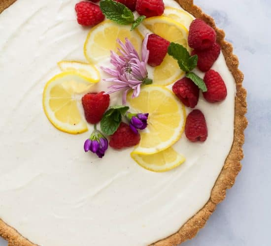 Creamy Lemon Tart Recipe with Almond Crust with flowers and berries on top
