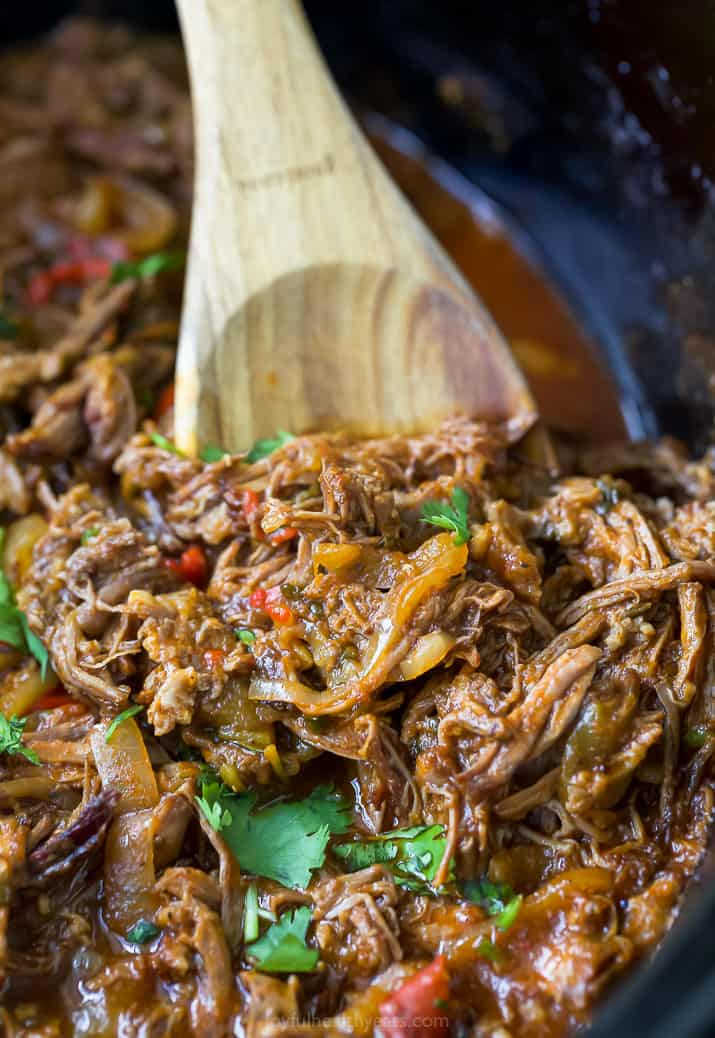 ropa vieja recipe (cuban shredded beef) in a crock pot with a spoon scooping the beef
