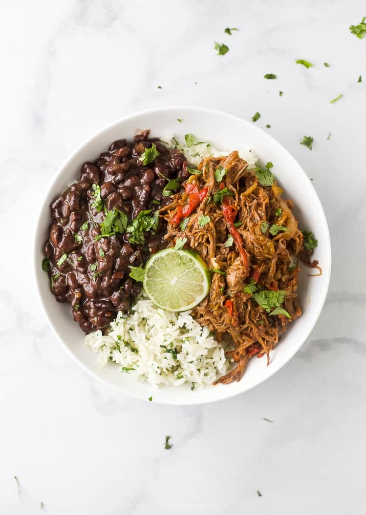 crock pot ropa vieja recipe (cuban shredded beef) in a bowl with rice and beans