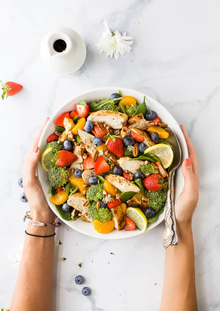 detox strawberry chicken salad with honey mustard dressing with hands around a bowl