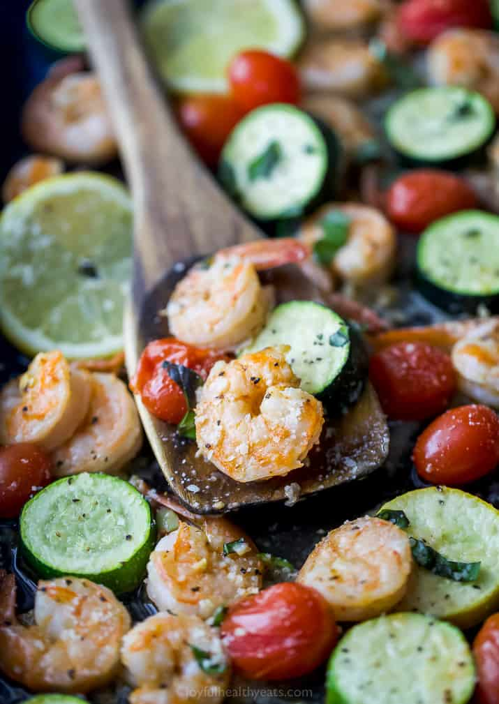 a wooden spoon scooping Easy Garlic Parmesan Sheet Pan Shrimp and Zucchini on a pan