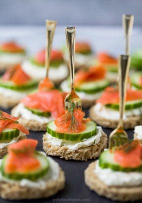 smoked salmon cucumber tea sandwiches on a serving tray with a small fork in them