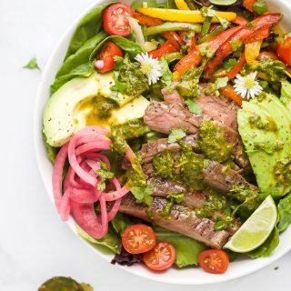 grilled fajita steak salad with chimichurri dressing in a bowl