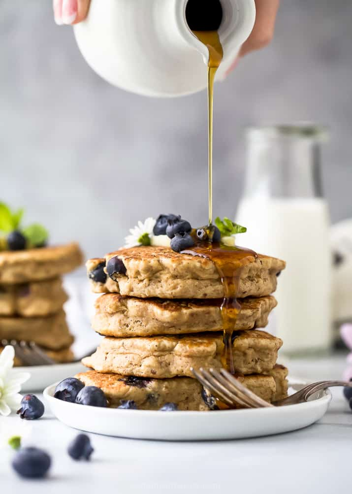 stack of healthy vegan blueberry pancakes with syrup being poured over them