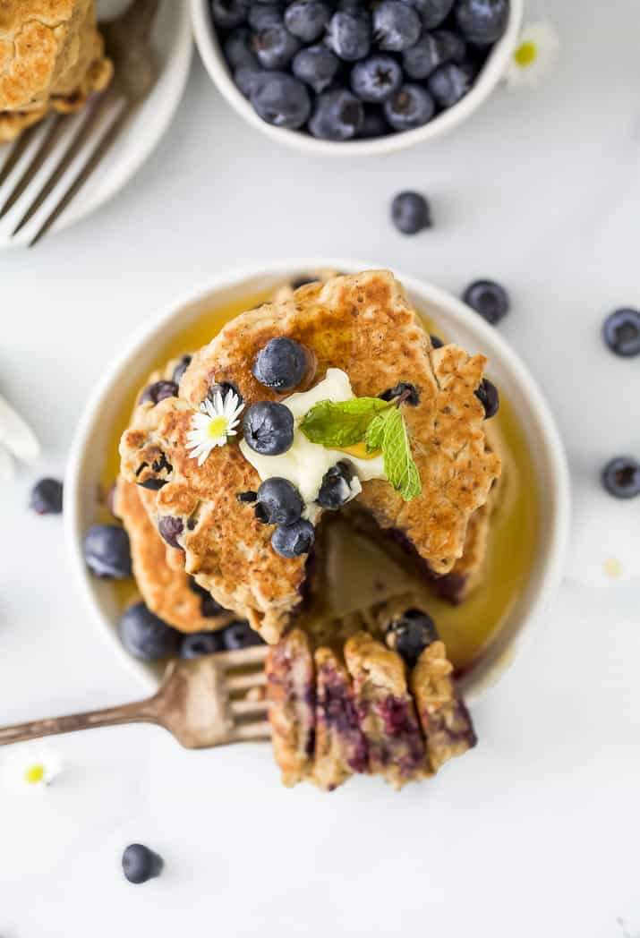 overhead photo of healthy vegan blueberry pancakes on a plate with butter on top