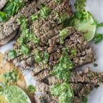 the best marinated grilled flank steak on a cutting board with chimichurri sauce