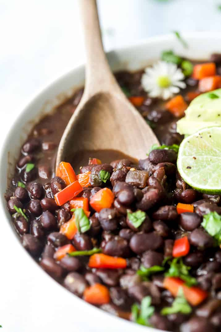 wooden spoon scooping mexican instant pot black beans