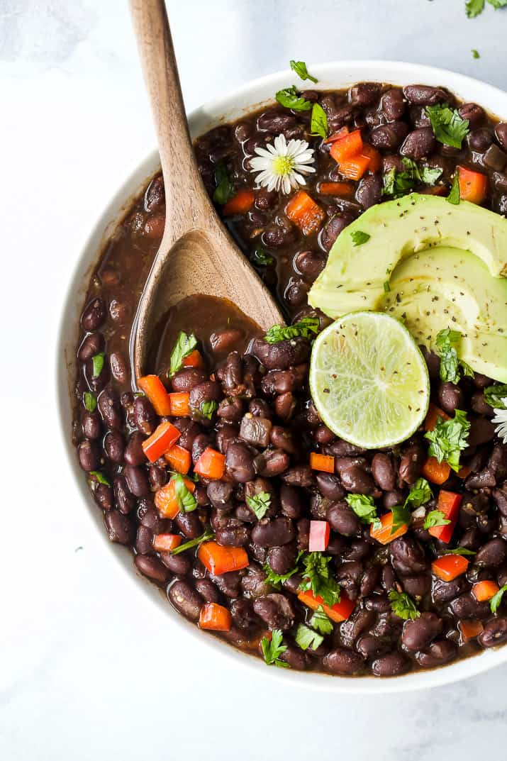 overhead photo of a wooden spoon scooping mexican instant pot black beans