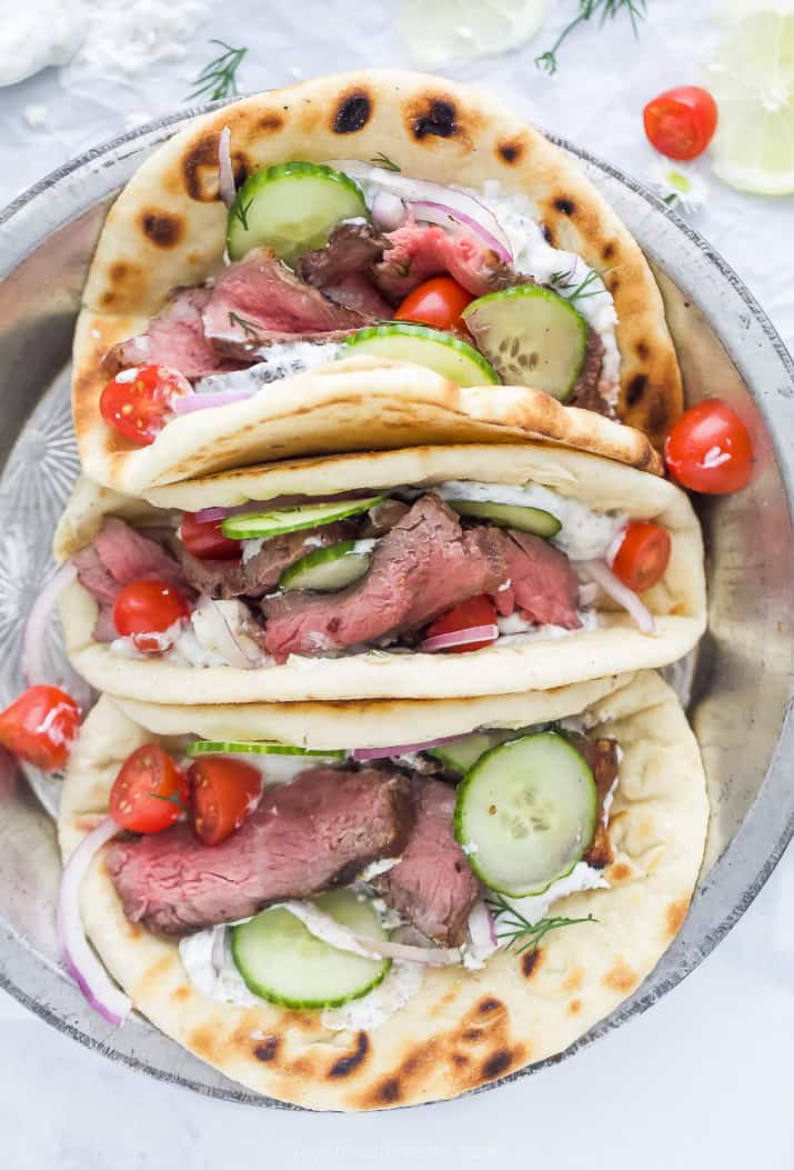 overhead photo of easy grilled steak gyros with tzatziki sauce and vegetables in a serving dish