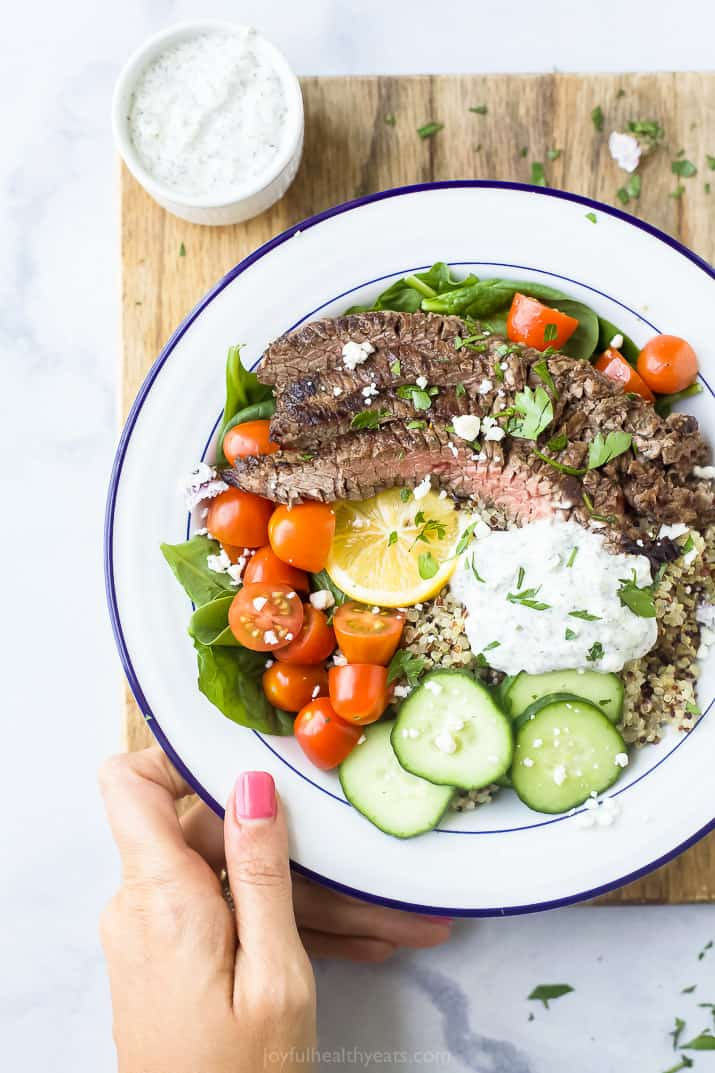easy mediterranean steak and quinoa bowls with tzatziki on a cutting board