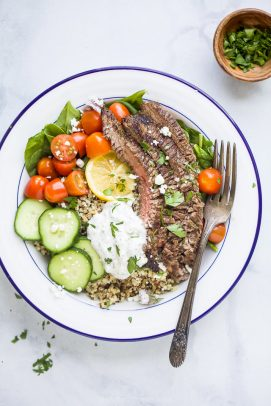 easy mediterranean steak and quinoa bowl topped with tzatziki